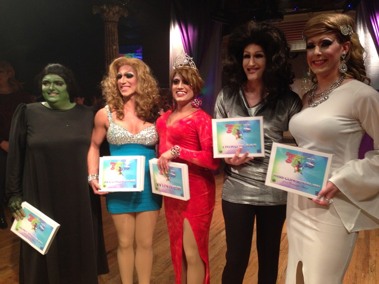 Alex Aguilar as Mia Deporte, center in red dress and crown, stands as the winner of the Dragging with the Stars contest, surrounded by the other contestants (L-R): Eric McCrickard (Tequila Mockingbird) of Cystic Fibrosis Foundation, Brad Joseph Claxton (Mimosa LaBousche) of Campus Pride, Tyler Daniels-Clyne (Carrie Concretia) of Don't H8 and Gary Carpenter (Nicole Monet) of Charlotte Pride.
