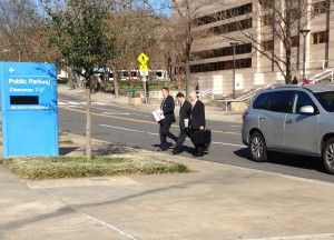 Federal officers walk out of the Charlotte-Mecklenburg Government Center carrying an evidence box.