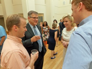 Andy Dews, left, and Tom Warshauer, center, chat at the open house.