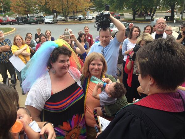 Amy Cantrell and Lauren White are married outside the Buncombe County Register of Deeds office on Friday evening by the Rev. Lisa Bovee-Kemper. Cantrell and White were among the first same-sex couples in North Carolina to receive legal marriage licenses and legally wed. Photo Credit: Campaign for Southern Equality.