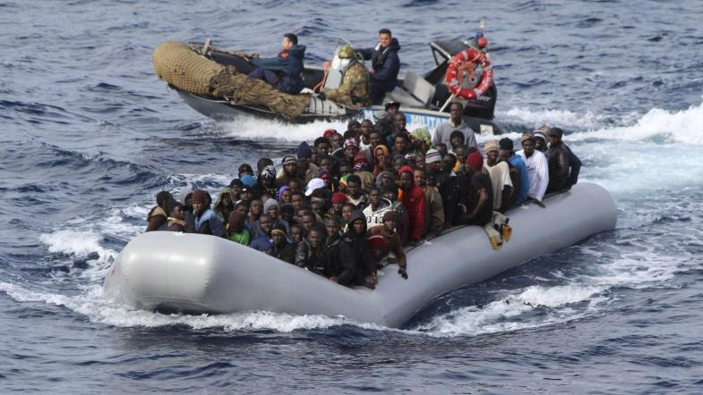 Migrants sit in a boat during a rescue operation by Italian navy off the coast of the south of the Italian island of Sicily