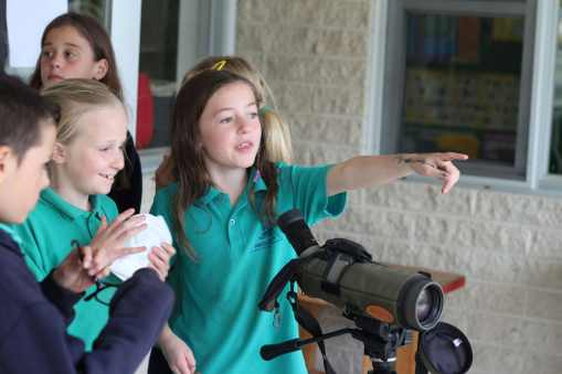 Students look through the scope used to spot Hooded Plovers on the beach to see how far they could see.