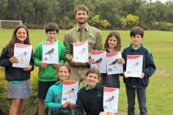 GORCC Education Coordinator Pete Crowcroft stands with students who proudly display their colouring in efforts to be displayed in the window of Bendigo bank, Anglesea.