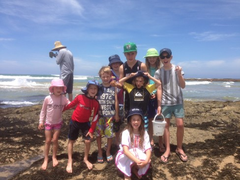 A group of young enthusiastic participants enjoy exploring the shallow rock pools for beach treasures.