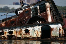The rusting and peeling paint of a retired service vessel in shallow waters of the Arthur Kill. (Gordon Donovan)