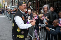Joe T. from Brooklyn, a member of the Nam Knights, hands out flags to spectators during the Veterans Day parade on Fifth Avenue in New York on Nov. 11, 2014. (Gordon Donovan)