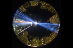 """In a photo taken with a fish eye lens, the two beams of light meet in the art installation """"The Tribute in Light"""" projecting in the night sky over Manhattan on Sept. 11, 2015. (Gordon Donovan/Yahoo News)"""