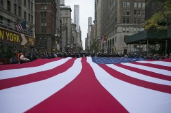 An American flag is draped across Fifth Avenue during the Veterans Day parade in New York on Nov. 11, 2015. (Gordon Donovan)