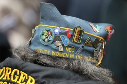 Highly decorated: the hat of a veteran is dressed up with pins as she listens to a speech before the Veterans Day parade. (Gordon Donovan)