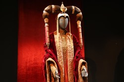 Amidala's Episode I Senate Gown is a bounty of luxurious fabrics. The loose-fitting robe was made in a velvet fabric decorated with bronze metallic, organza, enhanced with seed pearls on the collar and cuff facings. The underdress of silk taffeta was constructed using layers of pleated panels heavily decorated with antique beads. The Mongolian-inspired headdress was made in copper using an electro-forming technique and then gold plated. (Gordon Donovan/Yahoo News)