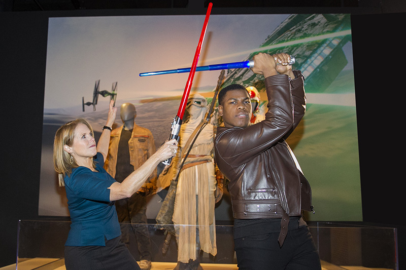 "Yahoo Global News Anchor Katie Couric summons the force as she battles actor John Boyega with light sabers at the ""Star Wars and the Power of Costume"" exhibition at Discovery Times Square in New York City on Dec. 2, 2015. Boyega stars as Finn in ""Star Wars: The Force Awakens."" (Gordon Donovan/Yahoo News)"