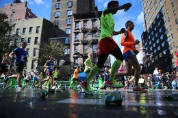 Runners step on used water cups discarded on the street during the 2016 New York City Marathon, Nov. 6, 2016. (Gordon Donovan/Yahoo News)