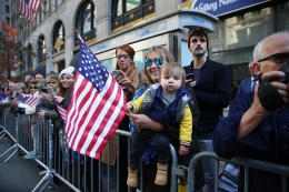 A woman and baby wave a flag as vets march during the Veterans Day parade on Fifth Avenue in New York on Nov. 11, 2016. (Gordon Donovan)