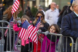 Young spectators wave flags as members of the armed forces march during the Veterans Day parade on Fifth Avenue in New York on Nov. 11, 2016. (Gordon Donovan)