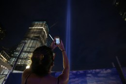 A woman takes a photo of the Tribute in Light with her mobile device at the National September 11 Memorial & Museum on Sept. 10, 2016. (Gordon Donovan/Yahoo News)
