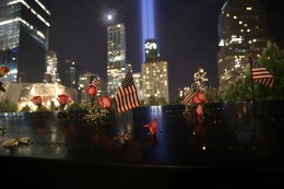 Flowers and flags lay on top of one of the panels at the North Pool of National September 11 Memorial & Museum as the Tribute in Light rises above the New York skyline on Sept. 10, 2016. (Gordon Donovan/Yahoo News)