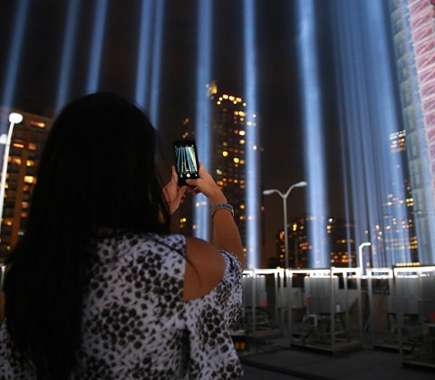A woman takes a photo of the Tribute in Light with her mobile device from the roof top of where the beams of lights are projected on Sept. 10, 2016. (Gordon Donovan/Yahoo News)