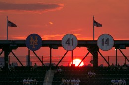 The sun begins to set just behind the retired numbers on a beautiful night for baseball as the Colorado Rockies and New York Mets play at Citi Field in New York, Friday, July 29, 2016. (Gordon Donovan)