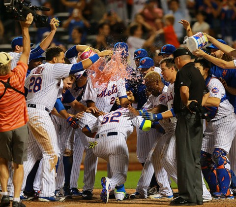 New York Mets Yoenis Cespedes is greeted at home plate by teammates after his home run with two outs in the bottom of the 10th inning to give the Mets a 2-1 victory against the Miami Marlins at Citi Field in New York, August 29, 2016. (Gordon Donovan)