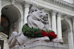Patience sits with a wreath around his neck on the south side of the main steps of the majestic Beaux-Arts building at Fifth Ave. and 42nd St. in New York City. (Gordon Donovan/Yahoo News)