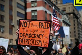 "A demonstrator holds up an orange sign and U.S. flag during the ""Not My President's Day"" rally on Central Park West in New York City on Feb. 20, 2017. (Gordon Donovan/Yahoo News)"