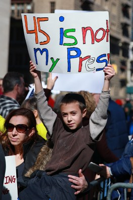 """A youngster with his mother holds up a sign during the """"Not My President's Day"""" rally at Central Park West in New York City on Feb. 20, 2017. (Gordon Donovan/Yahoo News)"""