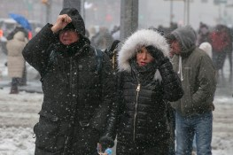 People hold their hoods as fight off high winds and snow as they cross the street in Times Square in New York City on Feb. 9, 2017. (Gordon Donovan/Yahoo News)