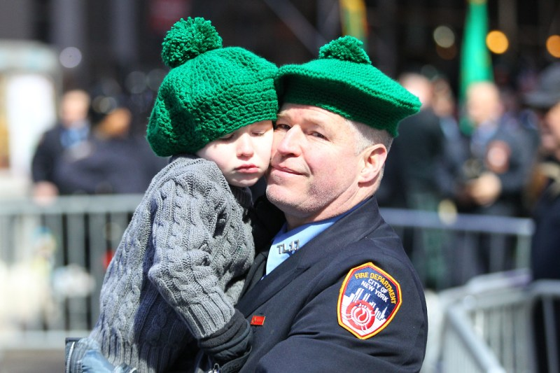 A member of the New York City Fire Department embraces his son while watching the St. Patrick's Day Parade, March 17, 2017, in New York. (Gordon Donovan/Yahoo News)