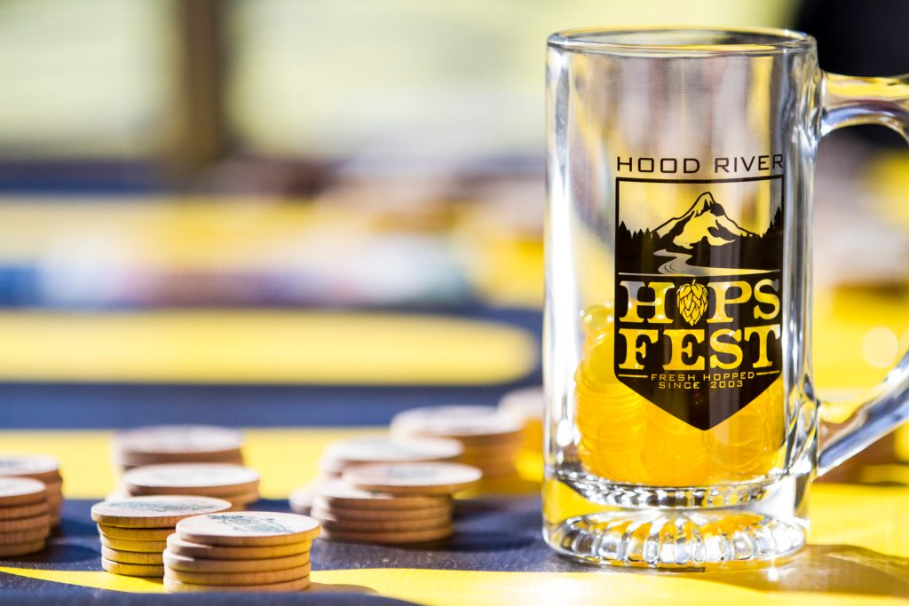 Close up photo of a glass mug of beer with a handle that reads Hood River Hops Fest. The sun is shining on stacks of wooden tokens beside it.