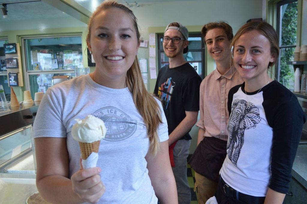 Picture of 4 smiling older teens inside Mike Ice Cream shop. The girl on the left is holding out a white ice cream cone to the camera.