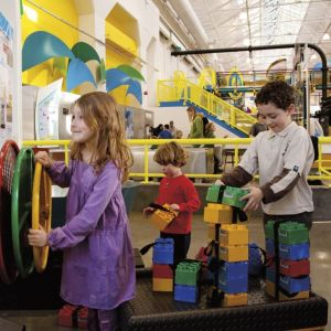 Photo of two boys playing with colorful large lego blocks at OMSI. A third girl in a purple dress has her hands on a yellow steering wheel.