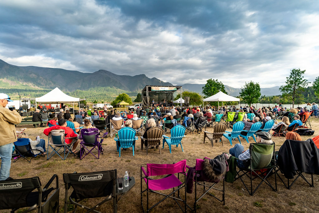 Photo of City of Stevenson Blues & Brews festival with stage in the middle and white tents on either side. We see the backs of the heads of several rows of people sitting in colorful chairs listening to the band on stage. The sky is blue and gray with dramatic clouds above and the cliffs of the Columbia Gorge in the distance.