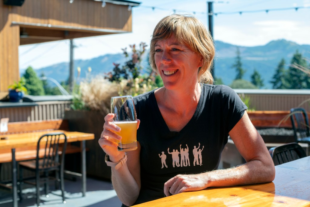 Smiling woman sits on an outdoor patio in the sun holding a small glass of beer. She is looking to the side and is wearing a black tshirt with a white logo for Everybody's Brewing (white silhouette of 7 people raising their glasses above their heads)