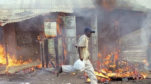 A member of the Luo tribe runs away from police and past a house reportedly owned by a Kikuyu which they ransacked and set ablaze by other members of his tribe during ethnic clashes in the central Kenyan town of Nakuru. (ROBERTO SCHMIDT, AFP/Getty Images)