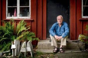 Gunar Eriksson sitter på trappan till hans röda stuga.