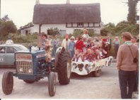 Duncan McGuffie of Woolstone driving a fete trailer into the entrance to the playing field, 1976.