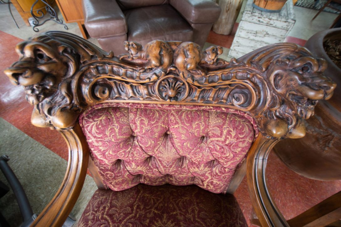 Vintage throne chair, featuring wood-carved lions and classic damask fabric.