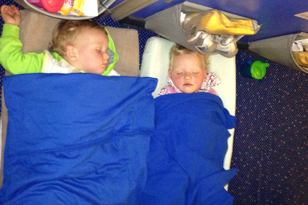 Chloë and Mason sleeping on the plane - Thailand with kids