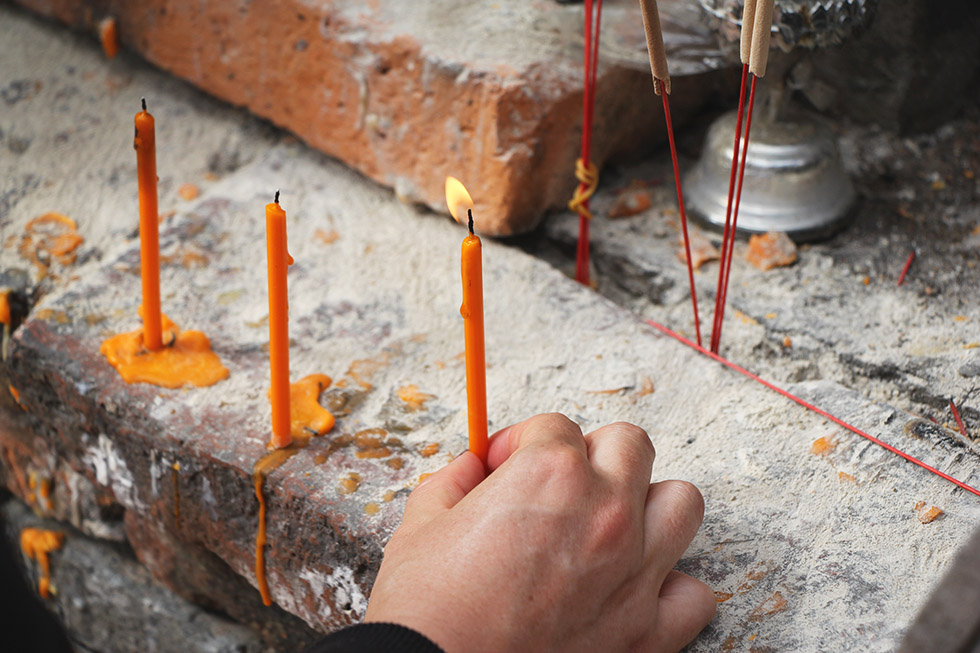 Lighting a candle at Wat Tilok Aram in Phayao