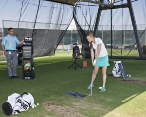 Image of woman golfer being fitted for clubs