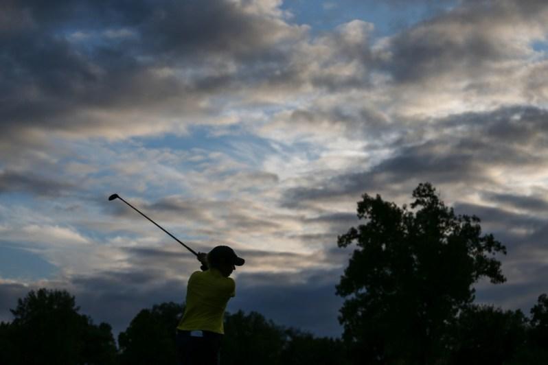 Image of woman golfer at twilight.