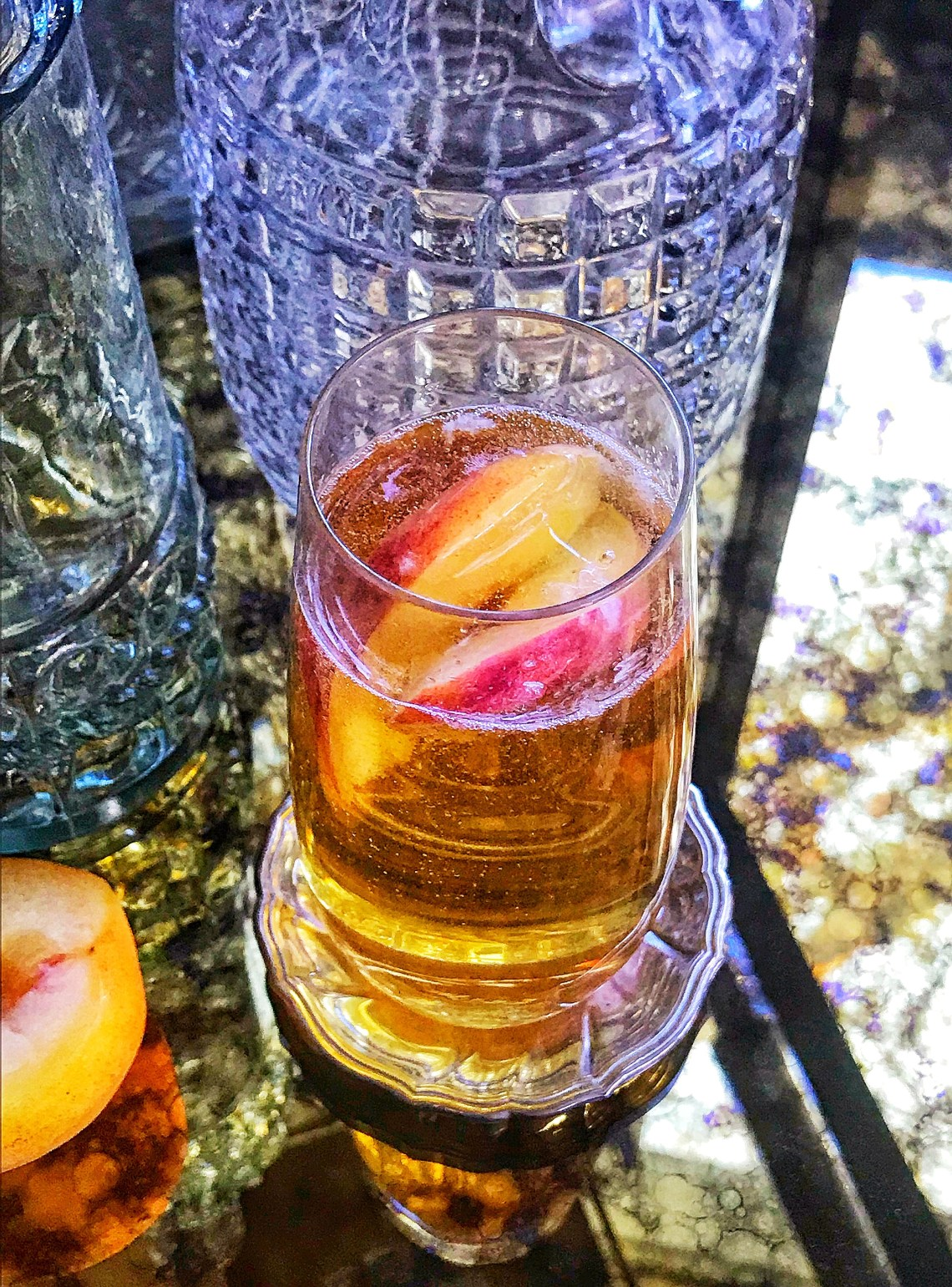 Bourbon and bubbles cocktail with sliced peaches