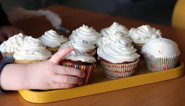 Une petite main gourmande attrape un cupcake au citron et au pavot