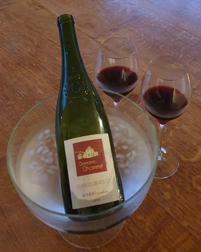 Bouteille de vin rouge dans seau avec des glaçons et deux verres