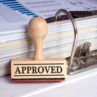 Approved - rubber stamp with text and binder with documents in the office