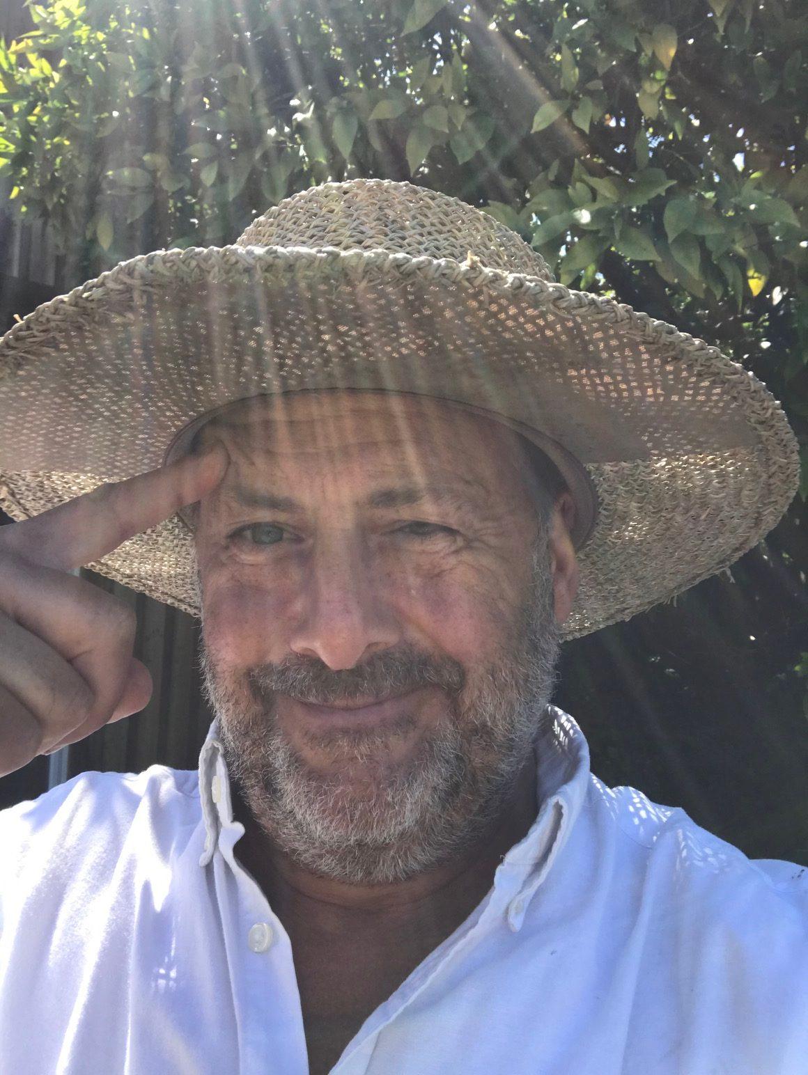 Sun-dappled picture of man in gardening sombrero.