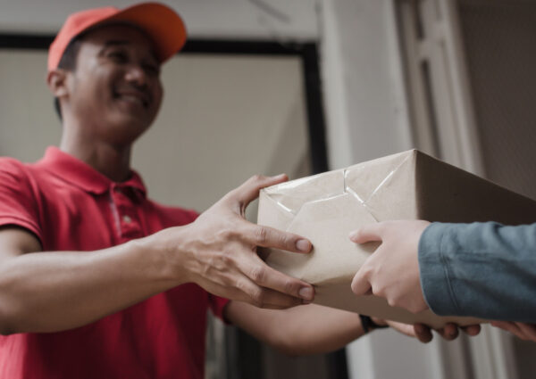 young delivery service man in red uniform smiling with woman customer receiving parcel post box from courier at home, cargo shipping, express delivery service, online shopping and logistics concept