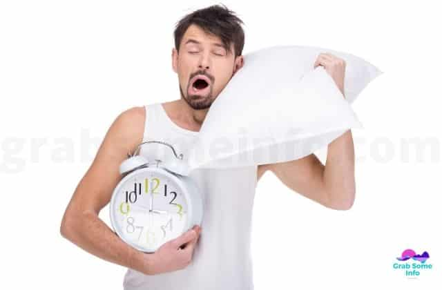 A man yawning with pillow and alarm clock in hand