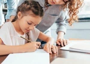 girl writing with mom