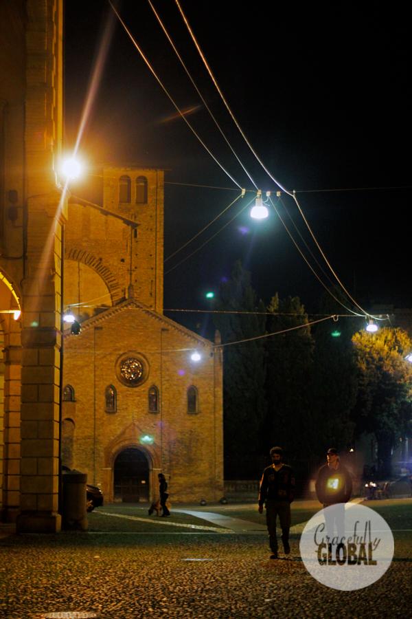 Two men walk through Bologna's Piazza San Francesco at night.